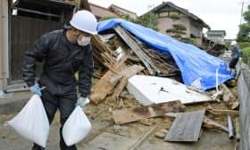 地震で倒壊した蔵にブルーシートをかぶせるボランティアの男性(23日、鳥取県北栄町)=共同