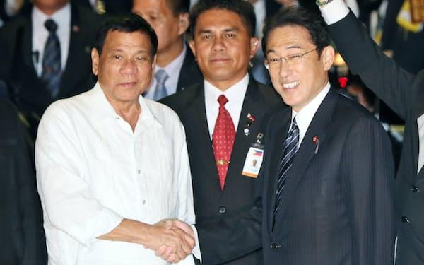 会食を前に岸田外相(右)と握手するフィリピンのドゥテルテ大統領(25日夜、東京・銀座)