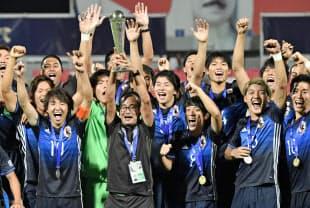 U-19アジア選手権で初優勝し、トロフィーを掲げ喜ぶ日本代表=共同