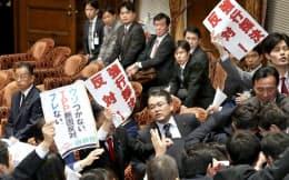 衆院TPP特別委で採決に反対し委員長席に詰め寄る民進、共産の委員ら。左端は山本農相(4日午後)
