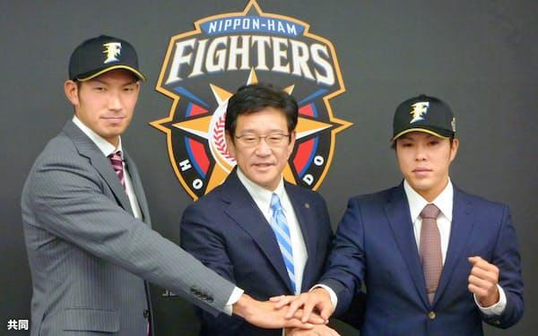 巨人からトレードで移籍し、日本ハムの栗山監督(中央)とポーズをとる大田泰示外野手(左)と公文克彦投手(4日、千葉県鎌ケ谷市)=共同