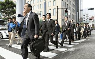 電通の東京本社に家宅捜索に向かう東京労働局の労働基準監督官ら(7日午前9時26分、東京都港区)=共同