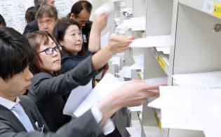 決算発表の資料を報道各社の棚に入れる企業の担当者(11日、東証)
