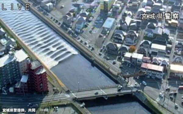 宮城県多賀城市の砂押川をさかのぼる、地震で発生した津波=宮城県警提供、共同