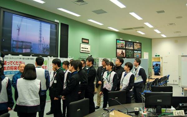 免震重要棟で東電担当者からの説明を聞く高校生たち