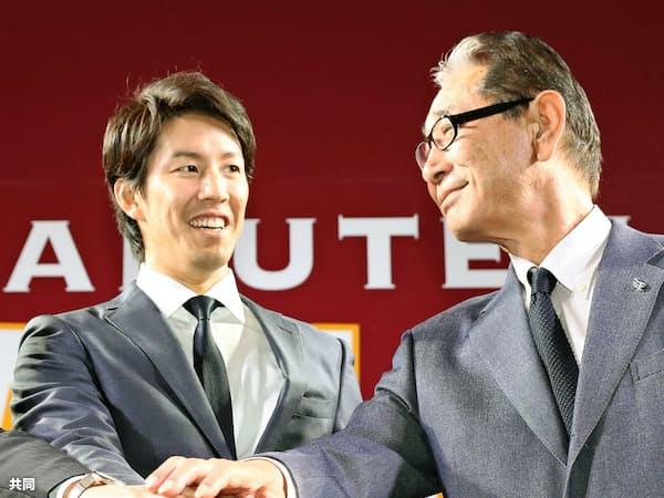 楽天と契約し、星野仙一球団副会長(右)と笑顔を見せる岸=共同