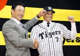 阪神の入団会見で金本知憲監督(左)とポーズをとる糸井=共同