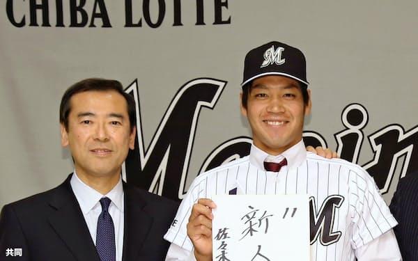 ロッテに入団が決まり、目標を書いた色紙を手にポーズをとる佐々木千隼投手。左は林球団本部長(8日、東京都内のホテル)=共同