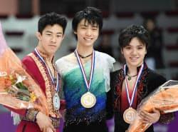 GPファイナル男子で4連覇を達成し、笑顔の羽生結弦(中央)。左は2位のネーサン・チェン、右は3位の宇野昌磨(10日、マルセイユ)=共同