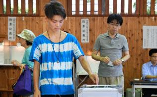 参院選で投票する18歳の有権者(手前)=7月10日、東京都新宿区