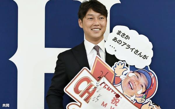 契約更改を終え、ボードを手に笑顔の広島・新井(15日、マツダスタジアム)=共同