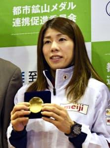 「都市鉱山」を活用したメダルのサンプルを手にする吉田沙保里選手=共同