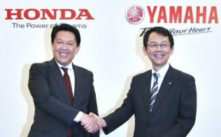 二輪車の生産、開発の提携を発表し、握手するホンダの青山真二取締役(左)とヤマハ発動機の渡部克明取締役(10月、東京都港区)