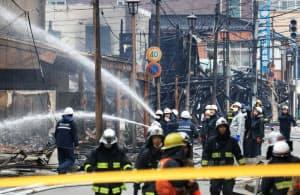 大規模火災から一夜明け、放水を続ける消防隊員ら(23日午前、新潟県糸魚川市)=小高顕撮影