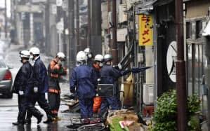 大火から一夜明け、火元の中国料理店周辺の実況見分をする警察官ら(23日午前、新潟県糸魚川市)=共同