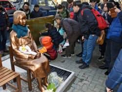 韓国・釜山の日本総領事館前の歩道に少女像が設置され、銘板に足を止める市民ら(30日)=共同