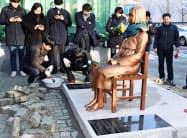 韓国・釜山の日本総領事館前の歩道に、従軍慰安婦被害を象徴する少女像を設置する市民団体のメンバーら=30日(共同)