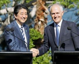 共同記者発表を終え、オーストラリアのターンブル首相(右)と握手する安倍首相=14日、シドニー(共同)