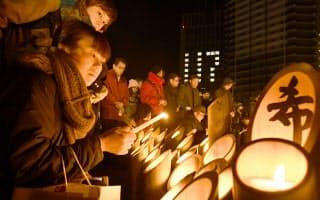 竹灯籠に火をともし犠牲者の冥福を祈る人たち(17日、神戸市中央区)