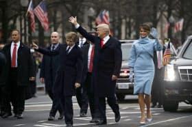 就任パレードで車から降りて手を振るトランプ大統領(20日、ワシントン)=ロイター