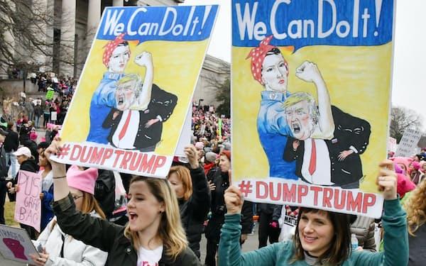 プラカードを掲げるデモの参加者(21日、ワシントン)=柏原敬樹撮影