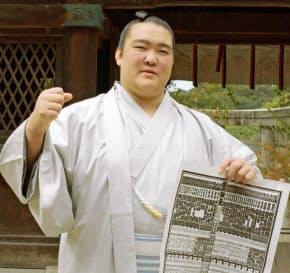 04年11月、新入幕を果たし、九州場所の番付表を手にする稀勢の里=共同
