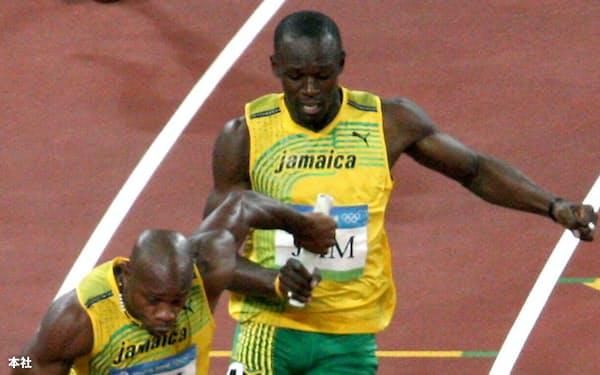 北京五輪・男子リレーで、第3走者のボルトからバトンを受け取るジャマイカのアンカー、パウエル=写真 瀬口蔵弘