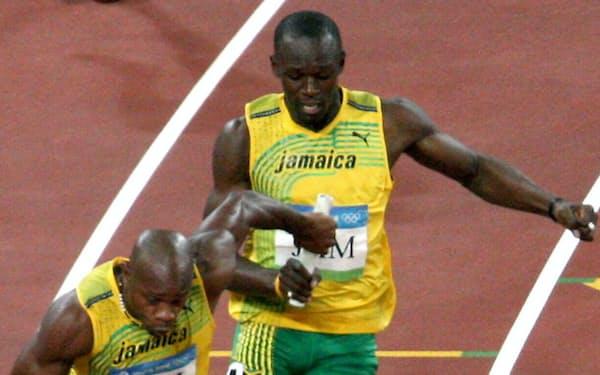 北京五輪・男子リレーで、第3走者のボルトからバトンを受け取るジャマイカのアンカー、パウエル=瀬口蔵弘撮影