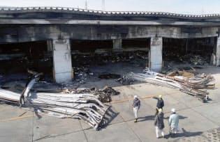 火がほぼ消し止められ、鎮圧状態となったアスクルの物流倉庫を見る関係者ら(22日午前、埼玉県三芳町)=共同