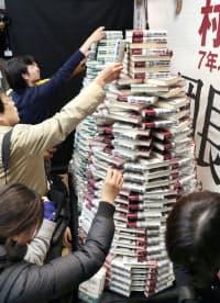 書店に積まれた村上春樹さんの新作を買い求める人たち(24日未明、東京都千代田区の三省堂書店神保町本店)