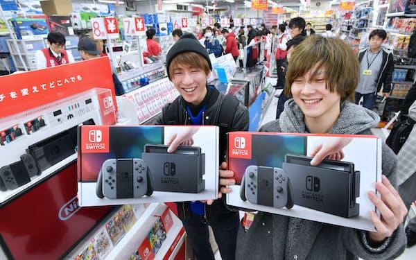 購入した「ニンテンドースイッチ」を手にする人たち(3日午前、東京都豊島区のビックカメラ池袋本店)=伊藤航撮影