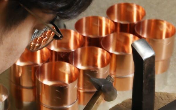 ブリキを金づちで打ち付け、蓋とぴったり合うように直径を広げる