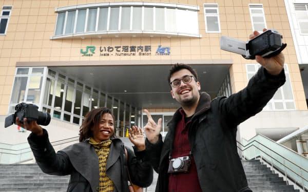 東北新幹線の「いわて沼宮内」駅に降り立ったフランス人のシャルル・サバスさん(右)と米国人のロレッタ・スコットさん。1日あたりの平均乗客数は85人(2015年)で、新幹線では日本一利用者数が少ないとされる駅を背にカメラを回す(2月22日、岩手県岩手町)