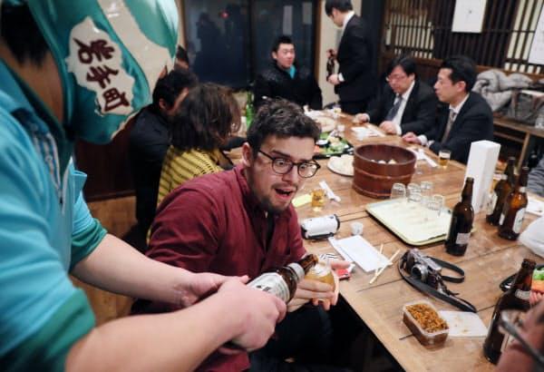 地元の飲み会でグラスを空ける間もなく、相次ぐビールのお酌に目を丸くするシャルルさん