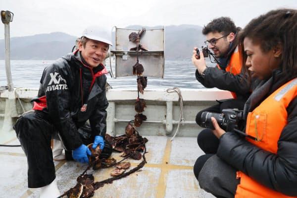 豊かな三陸の海で、ホタテの稚貝の生育を説明する漁師の佐々木淳さん(左)=2月23日、岩手県大船渡市