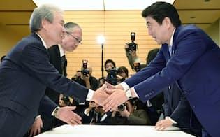 13日午後、首相官邸で残業時間の上限規制受け入れを伝え安倍首相と握手を交わす経団連の榊原会長(左手前)と連合の神津会長(同奥)=共同