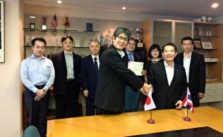 森・浜田松本法律事務所は昨年12月、タイの大手事務所を買収した(調印式でタイ側代表と握手する河井聡弁護士(左)ら)