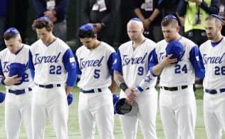 試合前、ユダヤ教徒が使う小さな丸帽子「キッパ」をかぶって整列し、国歌を聴くイスラエルの選手たち=共同