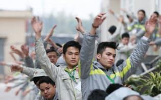 早朝、技能実習生の訓練学校でラジオ体操をするベトナム人(ハノイ)=上間孝司撮影