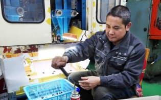 プラスチック容器工場で働くフィリピン人のアリストテル・デロさん(6日、韓国・富川)