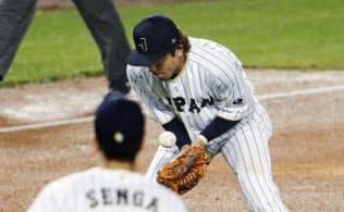 八回、米国のA・ジョーンズの打球をこぼす三塁手の松田。手前は千賀=共同