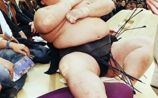 春場所13日目に日馬富士の寄り倒しで土俵下に落ち、痛みをこらえる稀勢の里