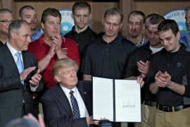 温暖化関連規制の見直しを指示する大統領令に署名したトランプ氏(28日、ワシントン)=ロイター