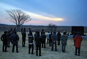 避難指示が解除され、慰霊碑の前で日の出を拝む住民ら(31日午前、福島県浪江町)=高木雄一郎撮影