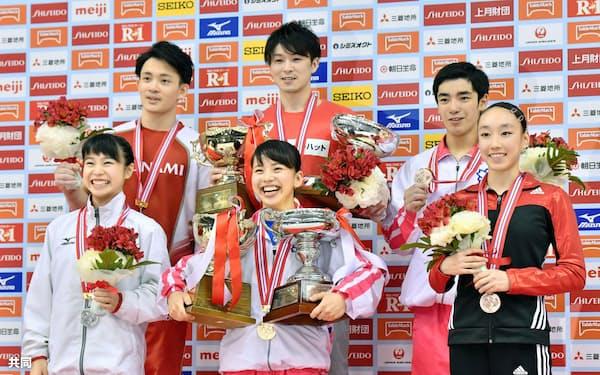 個人総合で優勝した女子の村上茉愛(前列中央)、男子の内村航平(後列中央)。前列左は女子2位の杉原愛子、同右は3位の梶田凪。後列左は男子2位の田中佑典、同右は3位の白井健三(9日、東京体育館)=共同