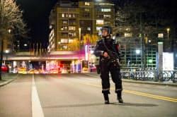 爆発物が見つかったオスロ中心部の地下鉄駅近くで警戒する警官(8日)=AP