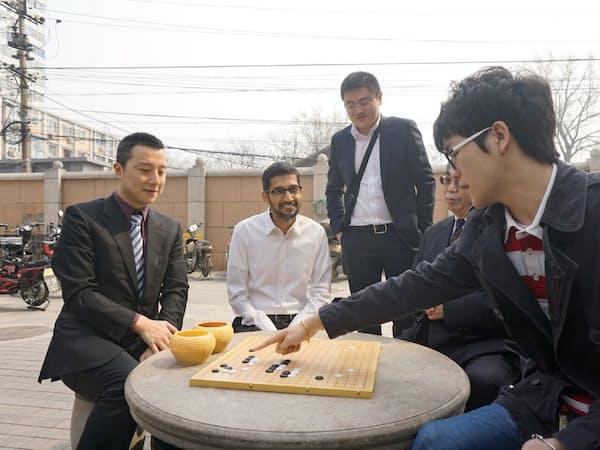 昨年、北京で柯潔九段(右端)からアルファ碁の手について説明を受けるグーグルのピチャイCEO(ディープマインド提供)