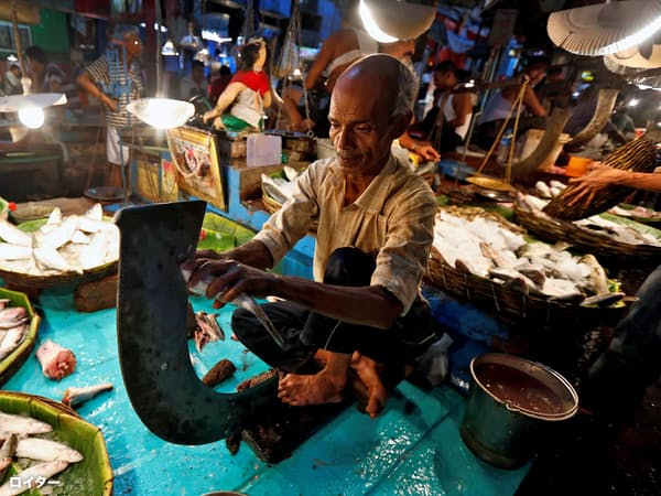A vendor cuts fish for a customer at a wholesale fish market in Kolkata, India, April 12, 2017. REUTERS/Rupak De Chowdhuri     TPX IMAGES OF THE DAY