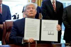20日、鉄鋼製品の輸入調査を命じた大統領令を掲げるトランプ氏(ワシントン)=ロイター