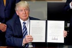 21日、財務省で大統領令に署名したトランプ米大統領(ワシントン)=ロイター